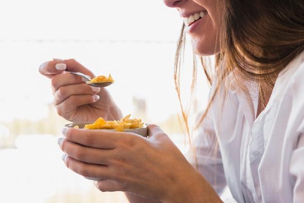 Close-up van jonge vrouw die cornflakes met lepel eet