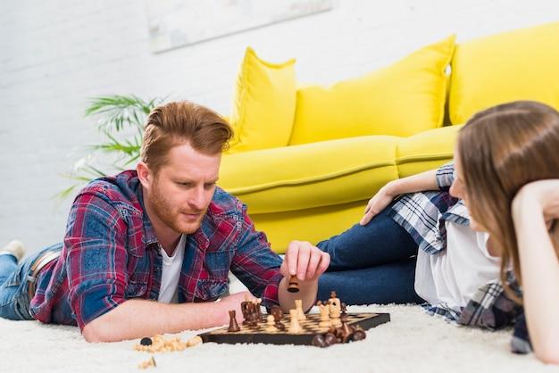 Close-up van jonge vrouw die de mens bekijkt die het schaakspel speelt