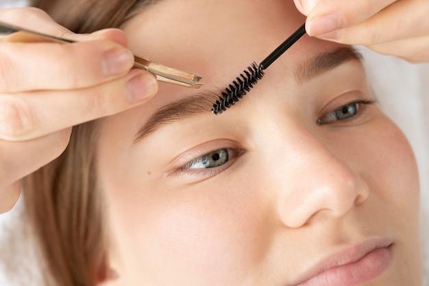 Close-up van jonge vrouw die een wenkbrauwbehandeling krijgt