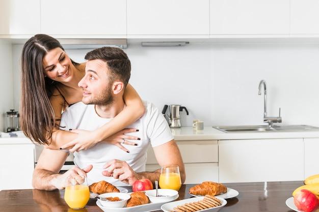 Close-up van jonge vrouw die haar vriend omhelst die ontbijt heeft