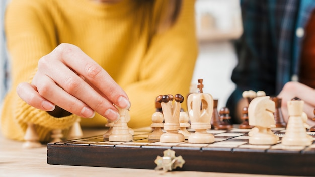 Close-up van jonge vrouw die het spel van de schaakraad speelt