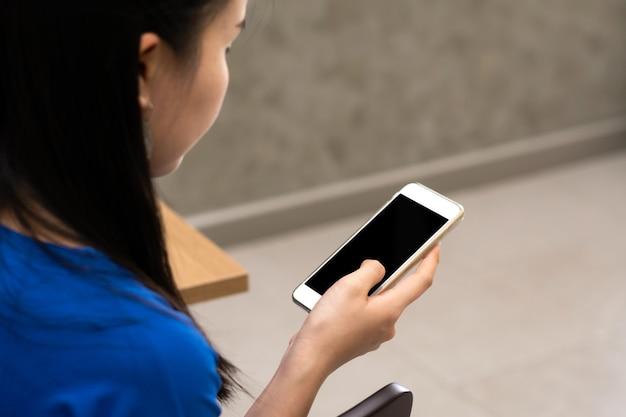 Close-up van jonge vrouw die mobiele telefoon vasthoudt en gebruikt. uitknippad opnemen in mobiele weergave.