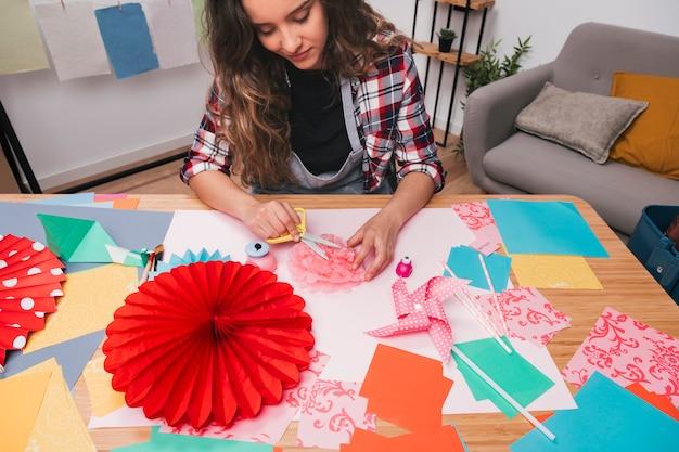 Close-up van jonge vrouw die mooie bloemambacht thuis maakt