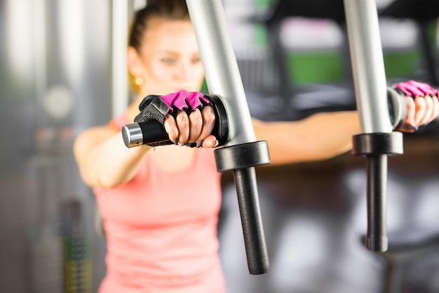 Close-up van jonge vrouw die oefening maakt bij de gymnastiek
