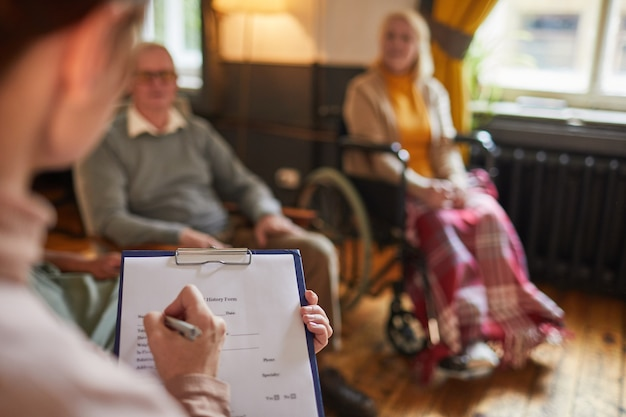 Close-up van jonge vrouw die op klembord schrijft tijdens therapiesessie in bejaardentehuis, kopieer ruimte