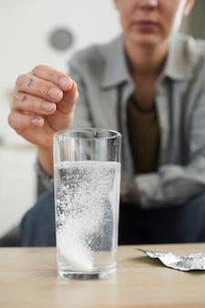 Close-up van jonge vrouw die pijnstiller van hoofdpijn drinkt na partij die zij op bank in de kamer zit