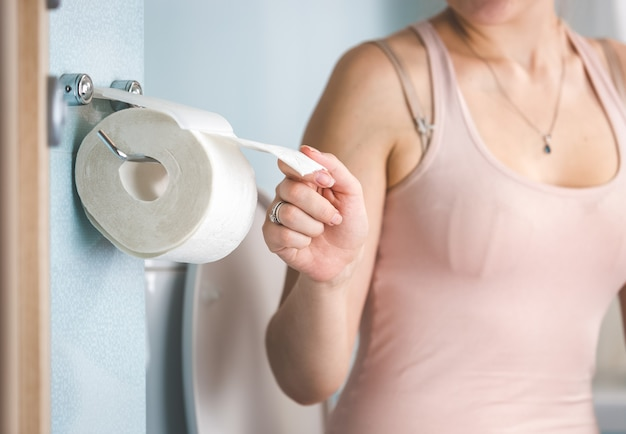 Close-up van jonge vrouw die toiletpapier gebruikt