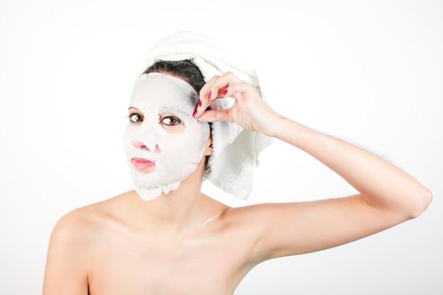 Close-up van jonge vrouw die wit masker van gezicht trekt