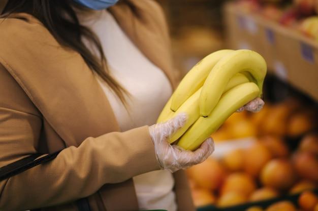 Close-up van jonge vrouw in beschermende handschoenen en gezichtsmasker mooie verse bananen in de hand houden