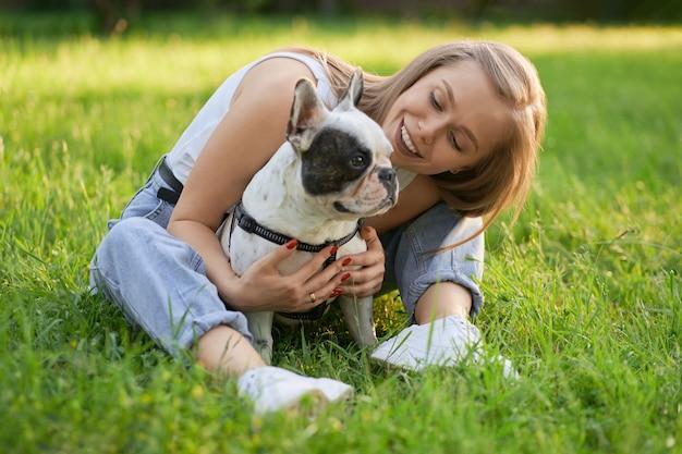 Close-up van jonge vrouw knuffelen volwassen franse bulldog in zomer park, zittend op het gras.