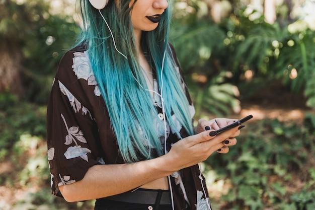 Close-up van jonge vrouw met behulp van de mobiele telefoon