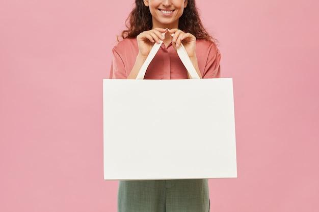 Close-up van jonge vrouw met grote witte papieren zak in haar handen en glimlachen
