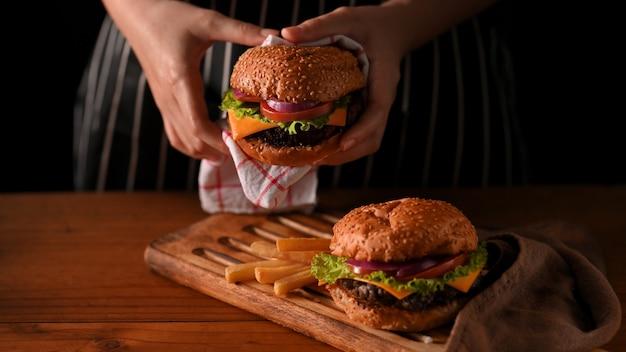 Close-up van jonge vrouw met rundvlees hamburgers met servet in restaurant met zwarte muur
