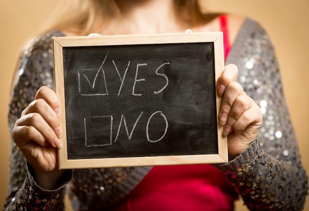 Close-up van jonge vrouw met schoolbord met aangevinkt