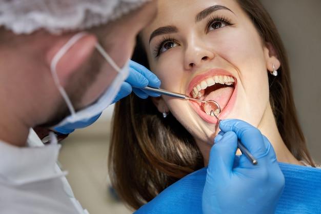 Close up van jonge vrouw met tandheelkundige check-up in tandartspraktijk. tandarts die een geduldig gebit met tandhulpmiddelen onderzoekt