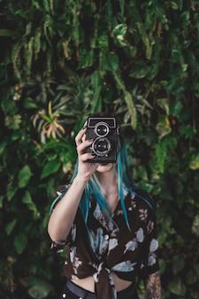 Close-up van jonge vrouw met vintage camera voor haar gezicht