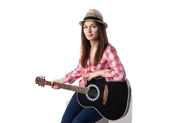 Close-up van jonge vrouw muzikant met gitaar zittend op een kubus. witte achtergrond.