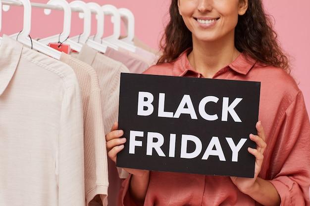 Close-up van jonge vrouw tijdens black friday in de winkel die kleren koopt