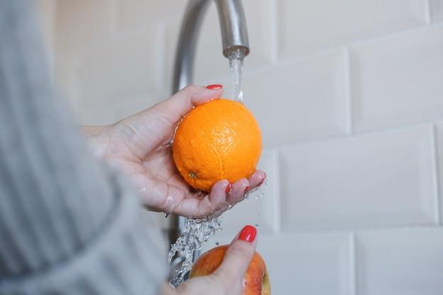 Close-up van jonge vrouw wast fruit om coronavirusinfectie te voorkomen