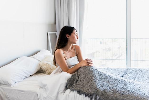 Close-up van jonge vrouw zittend op bed