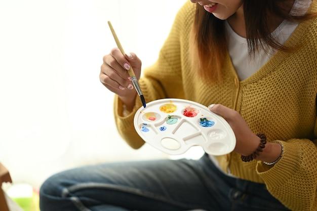 Close up van jonge vrouwelijke artiest zittend op de vloer met tube verf en het mengen van kleuren