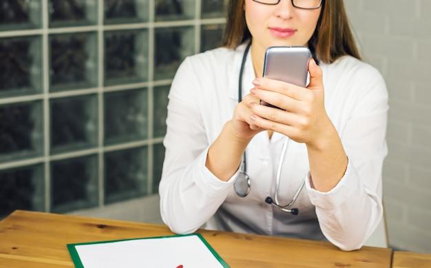 Close-up van jonge vrouwelijke arts met smartphone