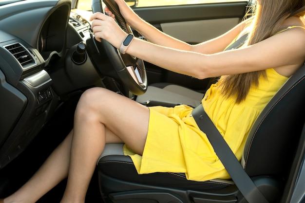 Close up van jonge vrouwelijke bestuurder vastgemaakt door veiligheidsgordel met lange benen in gele zomerjurk achter het stuur van een auto.