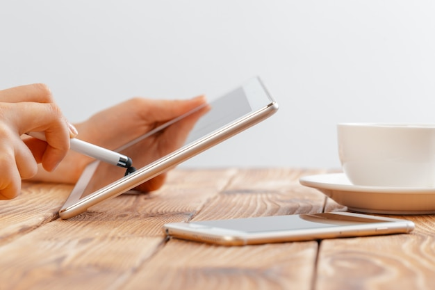 Close-up van jonge vrouwelijke handen die digitale tablet houden en ochtendmacchiato drinken.
