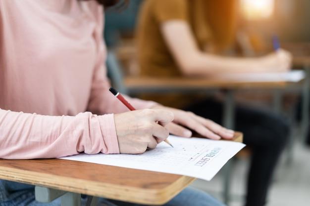 Close-up van jonge vrouwelijke universiteitsstudenten concentreren zich op het doen van examen in de klas. studente schrijft het antwoord van de examens op het antwoordblad in de klas.