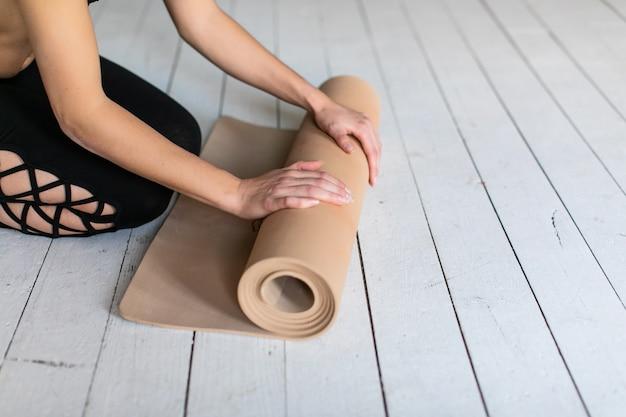 Close-up van jonge vrouwenhanden die yoga of geschiktheidsmat vouwen na de oefening van de praktijkrek bij yogaklasse. train thuis en rol de yogamat uit in de woonkamer.