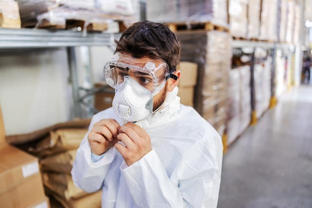 Close-up van jonge werknemer in steriel uniform en beschermend masker en bril op staande in magazijn en uniform ritsen. hij bereidt zich voor om het magazijn te steriliseren. corona uitbraak concept.