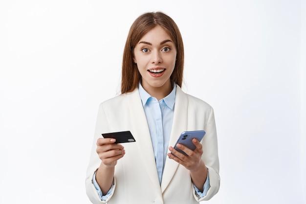Close up van jonge zakenvrouw in pak gemakkelijk online betalen met plastic creditcard en smartphone, online winkelen, mobiele telefoon vasthouden, verbaasd kijken naar de voorkant, witte muur