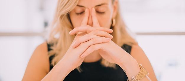 Close-up van jonge zakenvrouw met de handen over gezicht