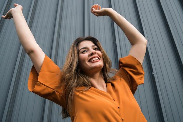 Close-up van jonge zelfverzekerde vrouw die lacht en viert terwijl hij buiten op straat staat