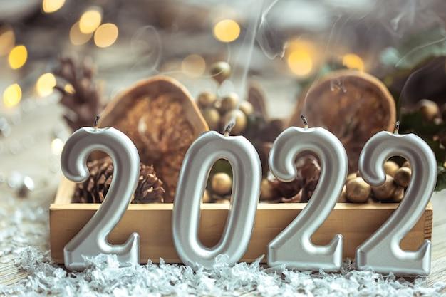 Close-up van kaarsen in de vorm van de nummers 2022 op onscherpe achtergrond met kerstdecor en bokeh.