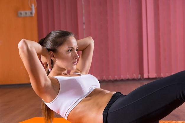 Close-up van kant profiel van jonge brunette vrouw dragen oefening kleding uitvoeren van kernversterkende oefeningen - abdominale crunches en been liften - op verdieping van dansstudio