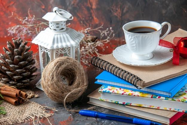 Close-up van kantoorbenodigdheden en pen kaneel limoenen conifer kegel en een kopje thee een bal van touw op donkere achtergrond