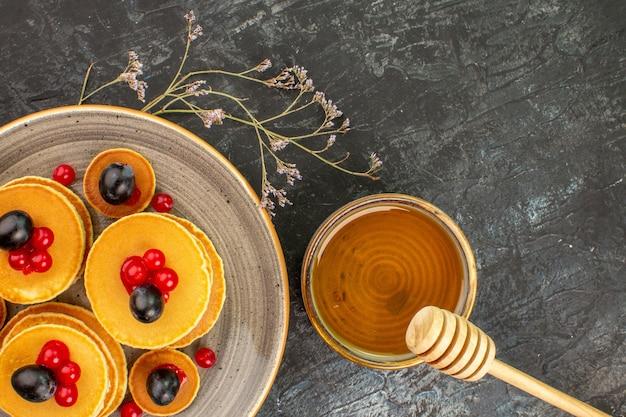 Close-up van karnemelk pannenkoeken en honing afbeelding voorraad op grijs