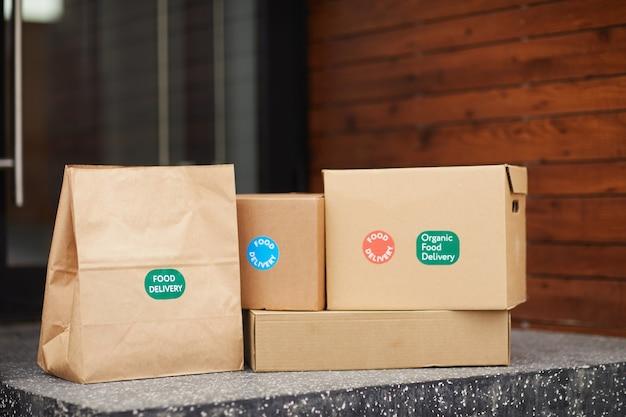 Close-up van kartonnen dozen en pakketten op de grond voor de deur buitenshuis