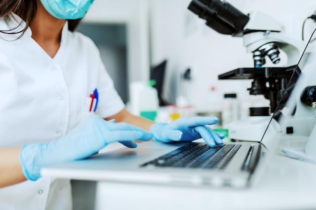Close-up van kaukasische vrouwelijke laboratoriumassistent resultaten van onderzoek op laptop typen.