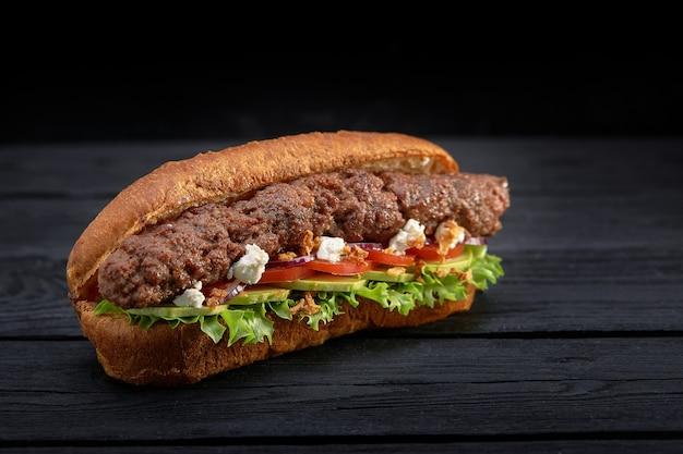 Close up van kebab sandwich op zwarte houten achtergrond. snel voedselconcept