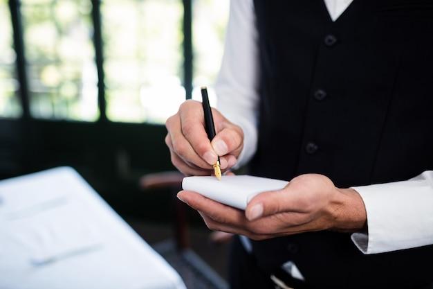 Close-up van kelner die een bestelling aanneemt die een vest draagt