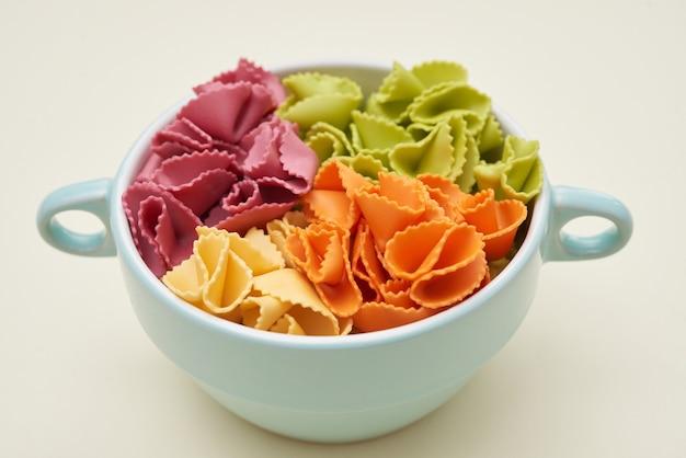 Close-up van keramische kom kleurrijke rauwe macaroni bereid om te koken, voedsel voor kinderen concept