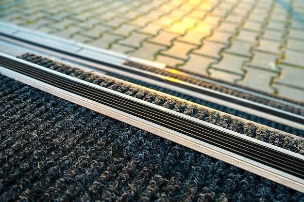 Close-up van keramische tegels die verandatrappen bedekken met rubberen anti-gladde strepen erop.
