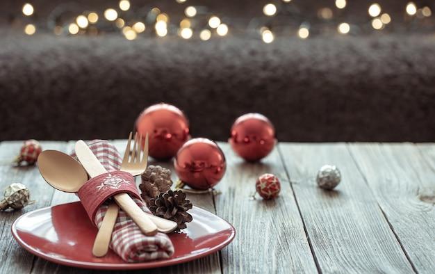 Close up van kerst feestelijke tafel instelling op wazig donkere achtergrond met bokeh, kopieer ruimte.