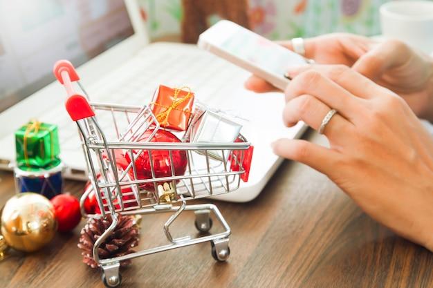Close-up van kerstcadeaus in winkelwagentje met vrouwen handen met behulp van mobiele telefoon, winkelen online