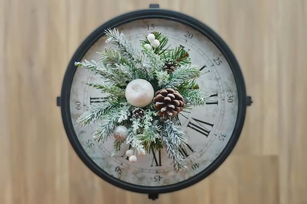 Close-up van kerstklok met nieuwjaarsversieringen. bekijk de top van de kerstboomtak met kegel en kunstmatige sneeuw op de klok. concept van kerstmis en gelukkig nieuwjaar. ruimte kopiëren