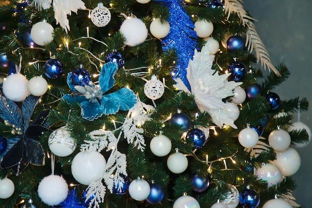 Close-up van kerstmis of nieuwjaar boom met decoratieve elementen en kunstmatige sneeuw. selectieve focus van kerstboom in het interieur van de woonkamer. concept van stijlvolle kerst achtergronden. ruimte kopiëren