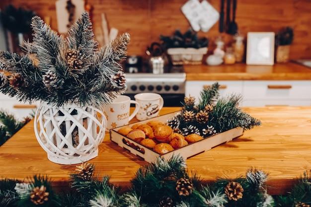 Close-up van keukentafel met vaas met dennentakken, twee keramische mokken en houten dienblad met zelfgemaakte cupcakes en dennenappels met dennentakken.