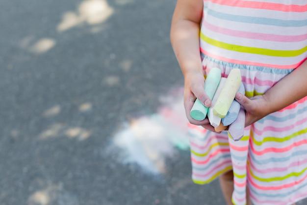 Close-up van kind dat gekleurd krijt voor tekening houdt.